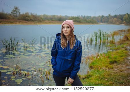 Stylish Sporty Brunette Woman In Trendy Urban Outwear Posing In Rainy Autumn Weather On The River Ba