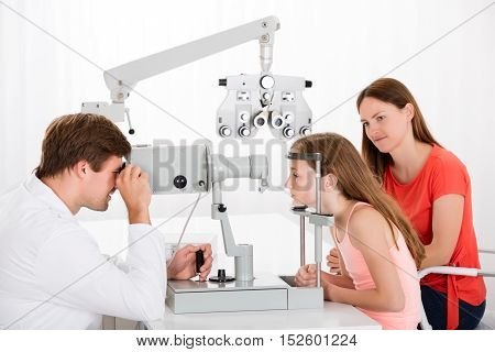 Male Optometrist Examining Eyesight Of Girl While Mother Sitting Beside Her