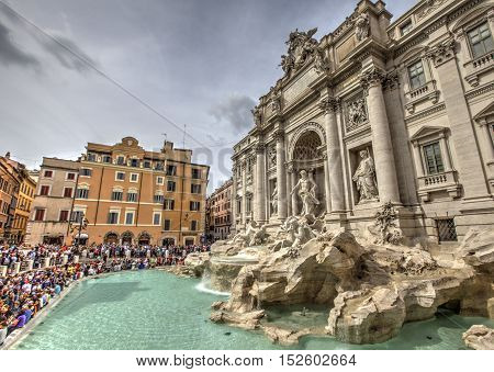 ROME, ITALY - SEPTEMBER 23, 2016: Tourists visiting the Trevi Fountain. Trevi Fountain is an iconic symbol of Imperial Rome. It is one of Rome's most popular tourist attractions.