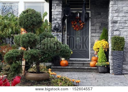 Front door to a Canadian house decorated with Halloween pumpkins.