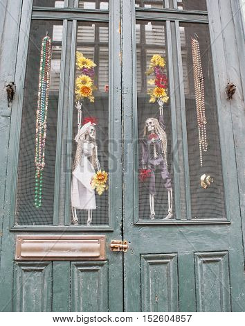 Voodoo wedding bride and groom in doorway in New Orleans, Louisisana - French Quater - Mardi Gras beads