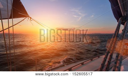 Beautiful sunset in the open sea with sailing yacht.