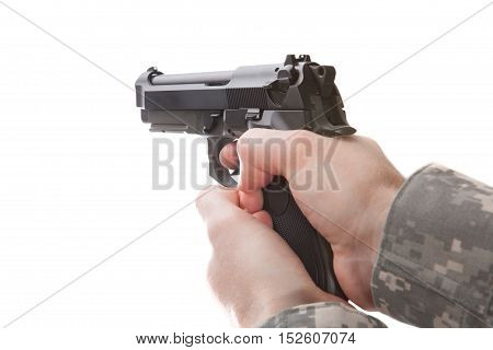 Man in military uniform holding hand gun and ready to use it