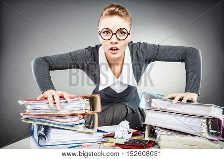 Job work frustration bureau paperwork workaholism concept. Upset secretary at her desk. Young office lady in glasses expressing anger.