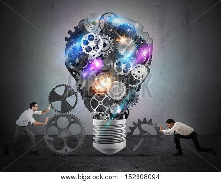 Business team push gears towards a great light bulb. build an idea concept