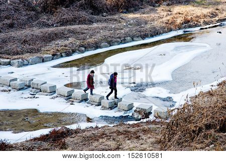 SEOUL SOUTH KOREA - FEBURARY 03 2016 - two women walking across an icey river on a cold winter day