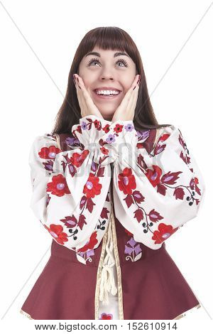 Natural Portrait of Caucasian Brunette Female Posing in National Flowery Dress. Showing Exclamation Touching Cheeks. Vertical Image Orientation
