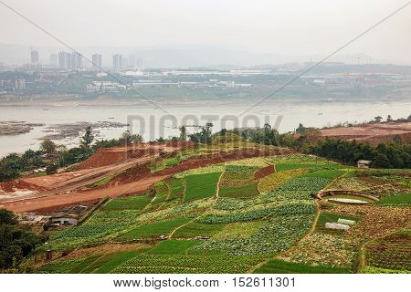 rural farming area by the yangtze river in Chongqing China with buildings in the mist