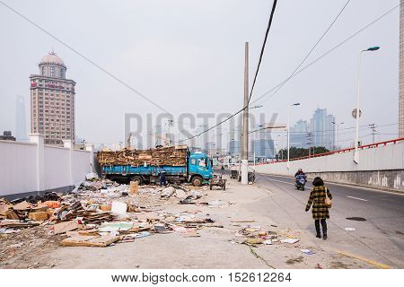 Shanghai China - March 14 2016: Garbage truck on a road near downtown Shanghai in a redeveloping area near central Shanghai.