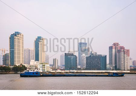 Architecture and boat on the Huangpu river with smog in Shanghai