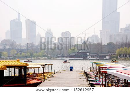 boats on Xuanwu Lake with buildings and Nanjing wall in the background