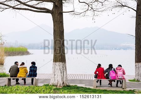 NANJING CHINA- MARCH 17: Chinese people sitting and talking by Xuanwu lake tourist area on March 17 2016 in Nanjing.