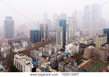 NANJING CHINA - MARCH 18: Xinjiekou financial district in Nanjing on a foggy day. This is the downtown area of Nanjing where many banks and offices can be seen on March 18 2016 in Nanjing.