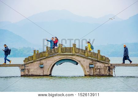 HANGZHOU CHINA - MARCH 23: Chinese people walking along a bridge on the West Lake with a couple taking a self portrait on March 23 2016 in Hangzhou.