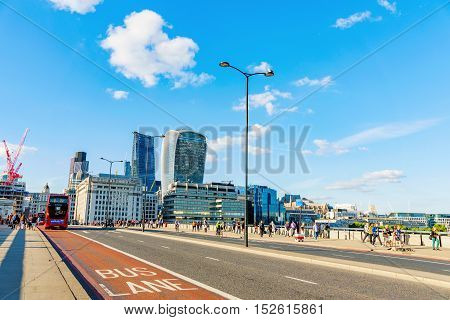 LONDON - JULY 06 2016: London Bridge is one of the main bridges in central London area. You can see many people walking across this bridge and Londons financial district in the distance on July 06 2016 in London.