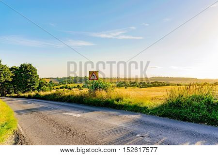 Bending road sign in landscape in countryside road