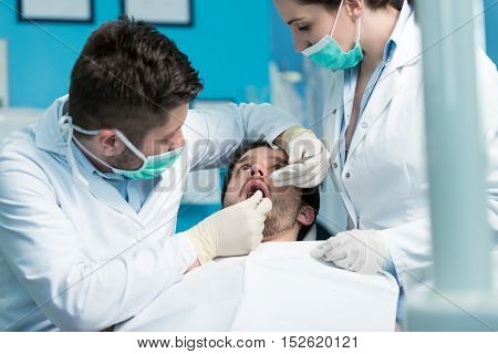 Dentistry Education. Male Dentist Doctor Teacher Explaining Treatment Procedure To Students Group In