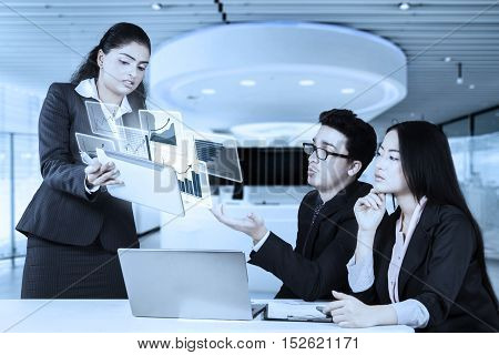 Indian businesswoman showing virtual chart on the tablet to discussion with her partner business in the office