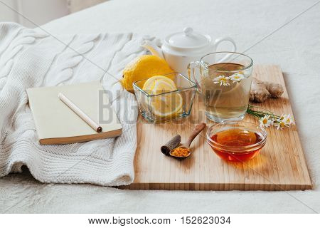 Herbal tea with chamomile flowers, turmeric and honey on a wooden board. Treatment of hot drink with ginger. Treatment of folk remedies in bed. Leisure with a book.