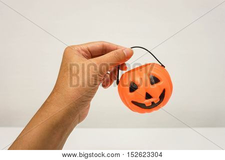 isolated close up woman hold orange Jack-O-Lantern bucket