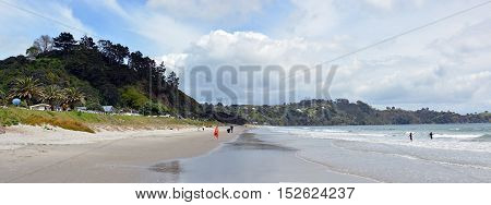 Auckland New Zealand - October 04 2016: Onetangi Beach panorama on Waiheke Island with people and waves in Spring.