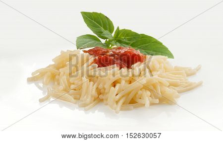 Isolated boiled vermicelli with fresh green basil on the white plate
