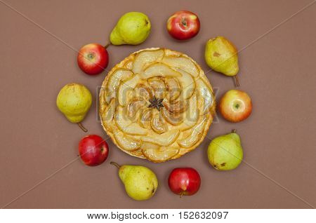 Whole tarte Tatin apple and pear tart pie with fruits on light brown background with copy space