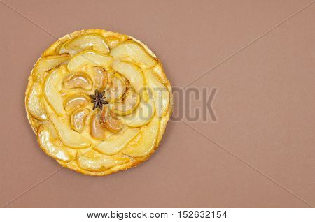 Whole tarte Tatin apple and pear tart pie isolated on light brown background with copy space