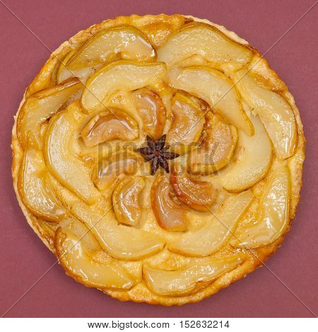 Whole tarte Tatin apple and pear tart pie isolated on claret background with copy space