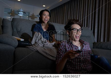 Laughing Asian couple watching funny movie at night