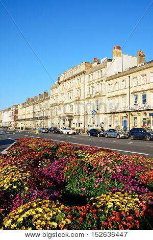 WEYMOUTH, UNITED KINGDOM - JULY 19, 2016 - Row of guesthouses along the Esplanade promenade with pretty flowerbeds in the foreground Weymouth Dorset England UK Western Europe, July 19, 2016.