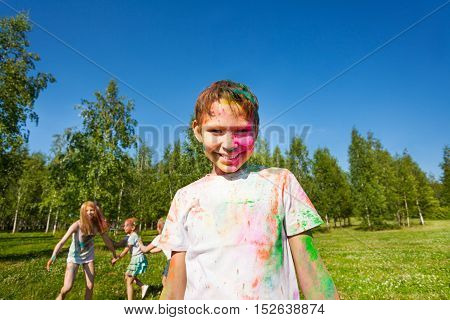 Portrait of happy ten years old boy painted in the colors of Holi festival