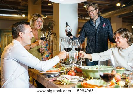 People cheering at celebration table with wine glasses.