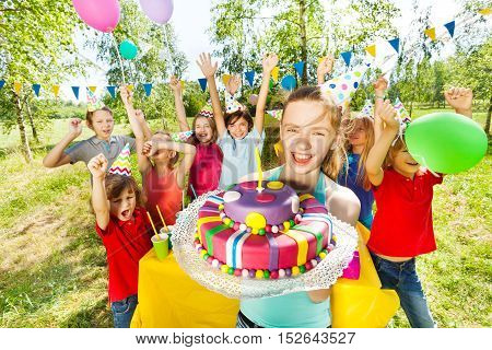 Portrait of smiling young girl in party hat holding birthday cake, while her friends having fun behind her