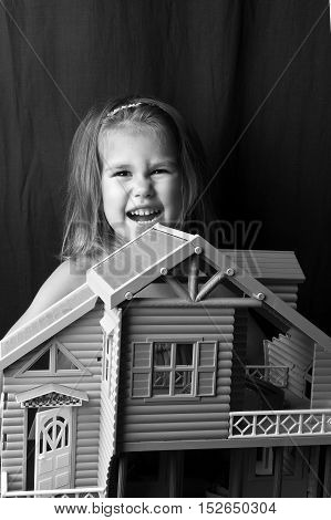 Girl playing with a baby doll house, dragging to a new location