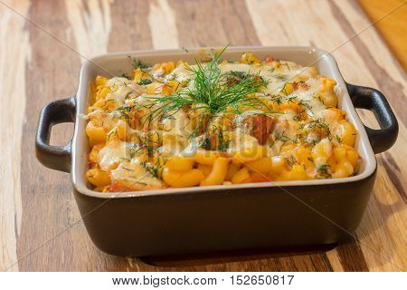 Macaroni or pasta with cheese and meat in square dish. Warm dish from the owen. Close up / macro photography.