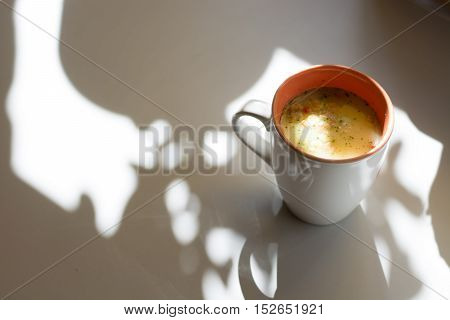 Cup / mug of soup. Bright rays light from the window.