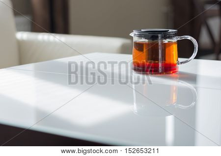 Transparent teapot on the white table. Natural light from the window.