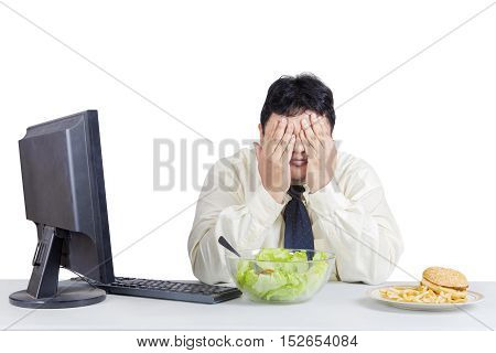 Overweight businessman try to diet while avoid temptation of foods with computer on the desk isolated on the white background