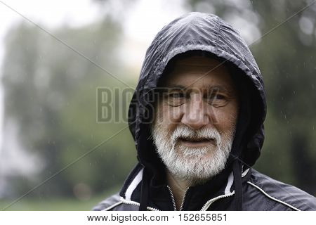 Mature caucasian gray man with beard and mustache in a park standing in the rain wearing hooded black sport jacket looking away from the camera with blurry background