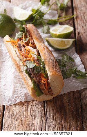 Traditional Vietnamese Banh Mi Sandwich With Pork, Cilantro, Carrot Close-up. Vertical