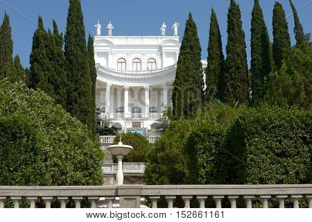 Bright White Empire Palace Behind Trees Of Park With Fountain.