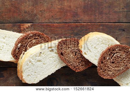Freshness sliced rye and wheat bread on old wooden background