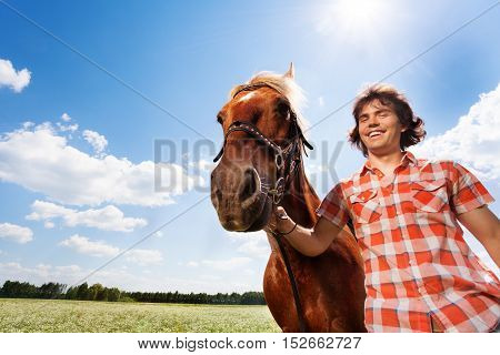 Portrait of smiling young man holding his beautiful horse by a bridle in flowery meadow