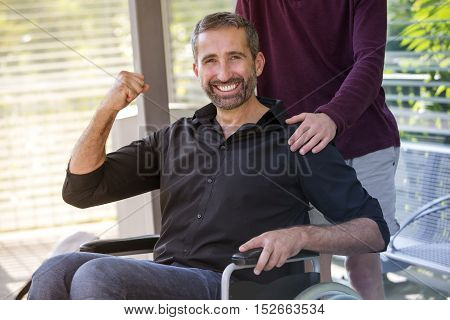 handsome man in wheelchair looking at camera and looking very optimistic