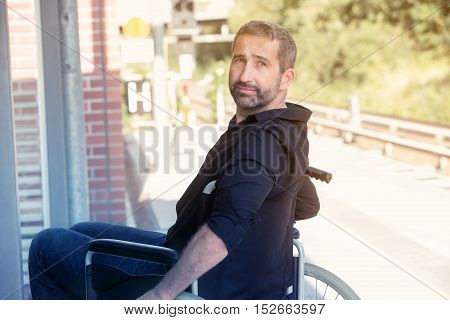 handsome man in his 40s sitting in wheelchair at train station