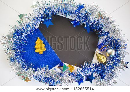 Christmas or New Year flat composition. Blue sparkling ribbon wreath. Fir tree toy and gift. Black paper with blank page. Season mockup for greeting message or advertisement. Festive photo background