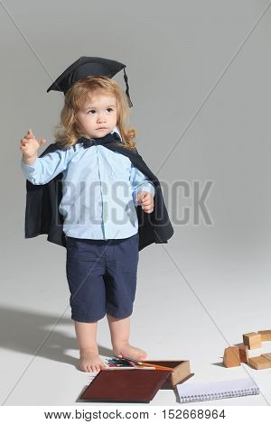 Small boy child with long blond hair in blue shirt black graduation gown and cap playing with pencil box isolated on white background