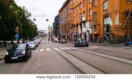 HELSINKI FINLAND - AUGUST 28 2016: Streets of the city center with parked cars and historical buildings. Many shops and cafes cloudy sky