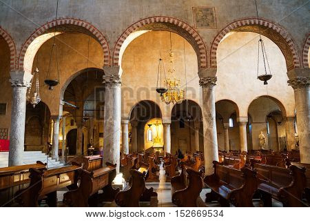 TRIESTE ITALY - MARCH 1 2016: Inside Roman Catholic Cathedral dedicated to Saint Justus. Popular landmark. Arches with rows and people